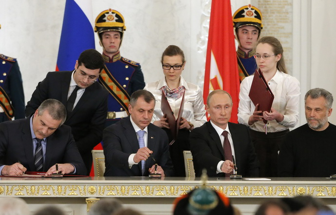 Russian President Putin, chief of Crimea's government Aksyonov, Crimean parliamentary speaker Konstantinov and Sevastopol Mayor Chaliy attend a signing ceremony at the Kremlin in Moscow