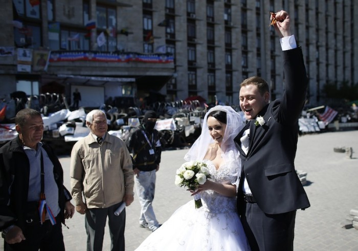 A newly married couple celebrate near a barricade outside a regional government building in Donetsk