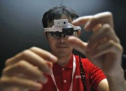 "A staff member of NTT DoCoMo Inc wears head-mounted ""intelligent glass"" at media preview of CEATEC JAPAN 2013 in Chiba"