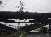 A truck drives under a destroyed railroad bridge which collapsed over a main road leading to the eastern Ukrainian city of Donetsk, near the village of Novobakhmutivka