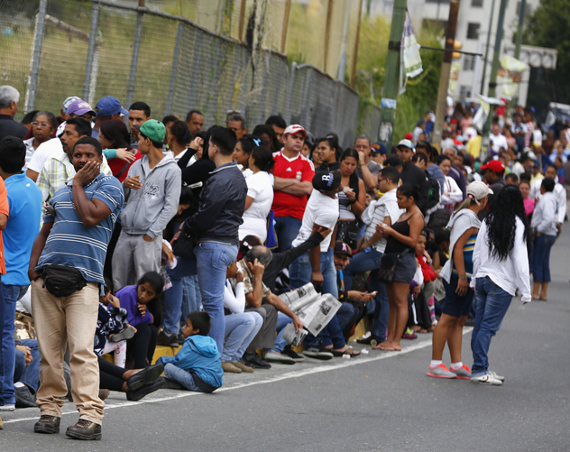 People line up outside a state-run Bicentenario supermarket in Caracas