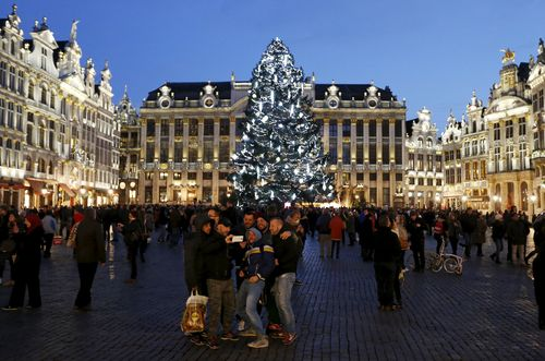 Tourists take a selfie photo in front of a Christmas tree on Brussels' Grand Place
