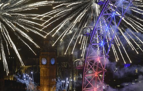 Fireworks explode around the London Eye wheel, the Big Ben clock tower and the Houses of Parliament to mark the beginning of the New Year in London
