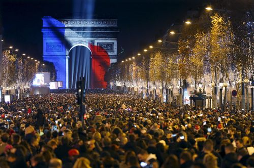 Revellers gather near the Arc de Triomphe which was lit with the colours of the French flag on the Champs Elysees Avenue in Paris