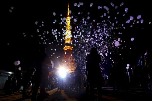 People release balloons at the turn of the New Year at a hotel in front of the landmark Tokyo Tower in Tokyo