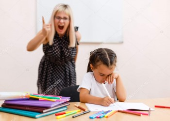 the teacher screams at the little schoolgirl. Little girl is sad at the desk in the classroom