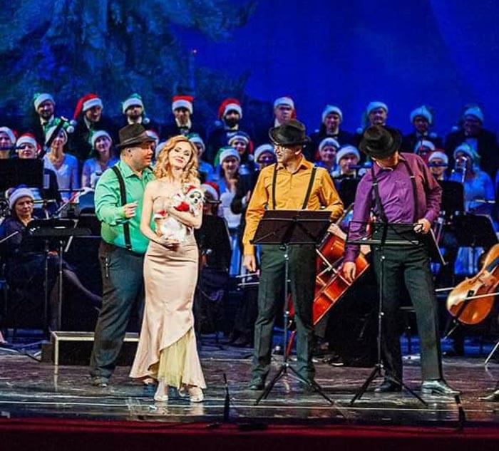 Зрителей поздравляют артисты оперы, балета, хор, оркестр, сказочные гномы и милый пёсик в образе Санты