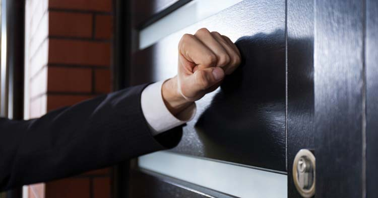 Hand knocking on the door